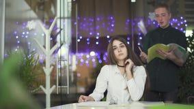Menina bonita que escuta o homem novo nos vidros ao sentar-se na tabela no escritório moderno com papéis na tabela video estoque