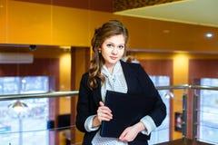 Menina bonita que está em um escritório e que guarda um portátil Imagens de Stock Royalty Free