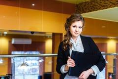 Menina bonita que está em um escritório e que guarda um portátil Fotos de Stock