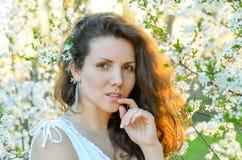 Menina bonita que está perto da árvore de florescência na mola Imagens de Stock Royalty Free