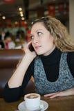 Menina bonita que fala em um telefone de pilha Foto de Stock