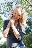 Menina bonita que fala no telefone móvel, telefone de pilha Fotos de Stock