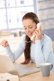 Menina bonita que fala no telefone usando o portátil em casa Imagens de Stock
