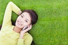 Menina bonita que fala sobre o telefone em um prado Imagens de Stock Royalty Free