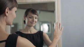 Menina bonita que faz a composição no olhar do banheiro no espelho A mulher toma sobre o olhar vista em um espelho Mulher lindo filme