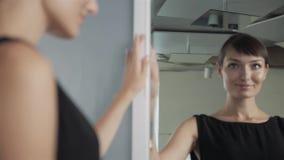 Menina bonita que faz a composição no olhar do banheiro no espelho A mulher toma sobre o olhar vista em um espelho Mulher lindo video estoque