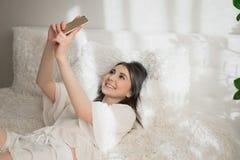 Menina bonita que faz a foto no telefone na cama foto de stock