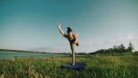 Menina bonita que faz a ioga exterior no nascer do sol Treinamento da menina da aptidão na manhã filme