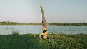 Menina bonita que faz a ioga exterior no nascer do sol Treinamento da menina da aptidão na manhã video estoque