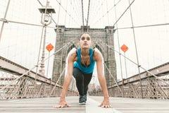 Menina bonita que faz o esticão no amanhecer antes de correr Ponte de Brooklyn e skyline de New York no fundo imagens de stock