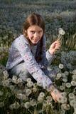 Menina bonita que faz o grupo de flores do dente-de-leão no campo bonito do dente-de-leão Fotos de Stock