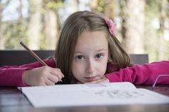 Menina bonita que faz trabalhos de casa no parque fotografia de stock royalty free