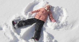 Menina bonita que faz um anjo da neve video estoque