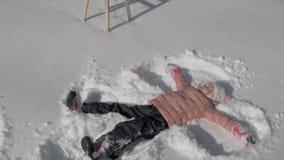Menina bonita que faz um anjo da neve vídeos de arquivo