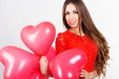 Menina bonita que guarda balões vermelhos do coração Fotografia de Stock Royalty Free