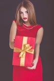 Menina bonita que guarda a caixa de presente do vermelho do Natal imagem de stock