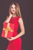 Menina bonita que guarda a caixa de presente do vermelho do Natal foto de stock royalty free