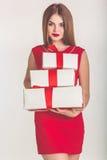 Menina bonita que guarda a caixa de presente vermelha do Natal imagem de stock