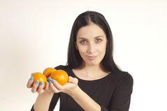 Menina bonita que guarda laranjas nas mãos Fotos de Stock Royalty Free