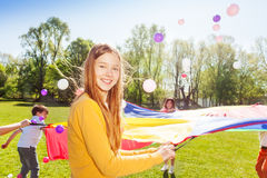 Menina bonita que guarda o paraquedas durante o jogo engraçado Imagem de Stock Royalty Free
