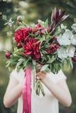 Menina bonita que guarda o ramalhete das peônias Imagem de Stock Royalty Free