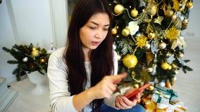 A menina bonita que guarda o telefone celular para acessórios festivos em linha do registro ou da reserva, senta-se no fundo video estoque