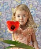 Menina bonita que guarda a tulipa Fotos de Stock Royalty Free