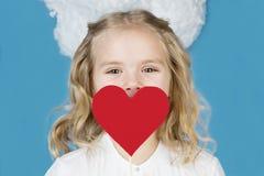 Menina bonita que guarda um coração em suas mãos Imagens de Stock Royalty Free