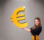 Menina bonita que guarda um sinal grande do euro do ouro 3d Imagens de Stock