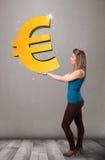 Menina bonita que guarda um sinal grande do euro do ouro 3d Foto de Stock