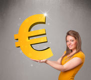 Menina bonita que guarda um sinal grande do euro do ouro 3d Imagens de Stock Royalty Free