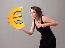 Menina bonita que guarda um sinal grande do euro do ouro 3d Imagem de Stock Royalty Free