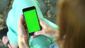 Menina bonita que guarda um smartphone nas mãos de uma tela verde do verde da tela, mão do homem que guarda o telefone esperto mó video estoque