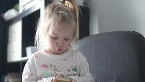 Menina bonita que guarda um telefone celular em suas mãos e que olha a tela vídeos de arquivo