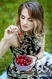 Menina bonita que guarda uma bacia de cerejas Verão quente O conce imagem de stock
