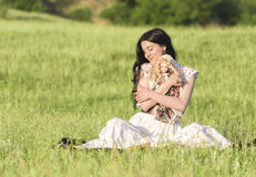 Menina bonita que guarda uma boneca Fotografia de Stock Royalty Free