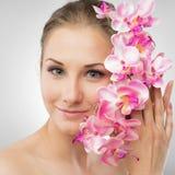 Menina bonita que guardara a flor da orquídea em suas mãos Fotos de Stock Royalty Free