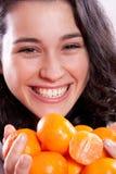Menina bonita que guardara tangerinas Fotografia de Stock