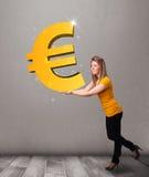 Menina bonita que guardara um sinal grande do euro do ouro 3d Foto de Stock