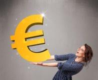 Menina bonita que guardara um sinal grande do euro do ouro 3d Imagem de Stock Royalty Free