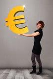 Menina bonita que guardara um sinal grande do euro do ouro 3d Fotografia de Stock Royalty Free