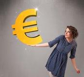 Menina bonita que guardara um sinal grande do euro do ouro 3d Imagens de Stock