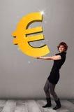 Menina bonita que guardara um sinal grande do euro do ouro 3d Imagens de Stock Royalty Free