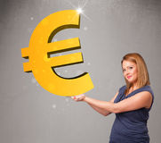Menina bonita que guardara um sinal grande do euro do ouro 3d Fotos de Stock Royalty Free