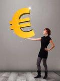 Menina bonita que guardara um sinal grande do euro do ouro 3d Fotografia de Stock