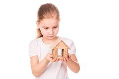 Menina bonita que guardara uma casa do modelo do brinquedo. Comprando um conceito da casa. Imagem de Stock Royalty Free