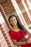 Menina bonita que inclina-se contra uma parede de tijolo Imagem de Stock