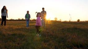 Menina bonita que joga a bola com sua família A mamã e as crianças jogam com a criança pequena com bola do bebê em um parque em video estoque