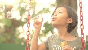 Menina bonita que joga bolhas de sabão no balanço video estoque