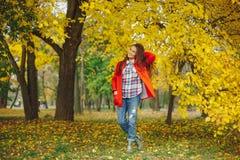 Menina bonita que joga com cabelo ao andar na paridade do outono foto de stock